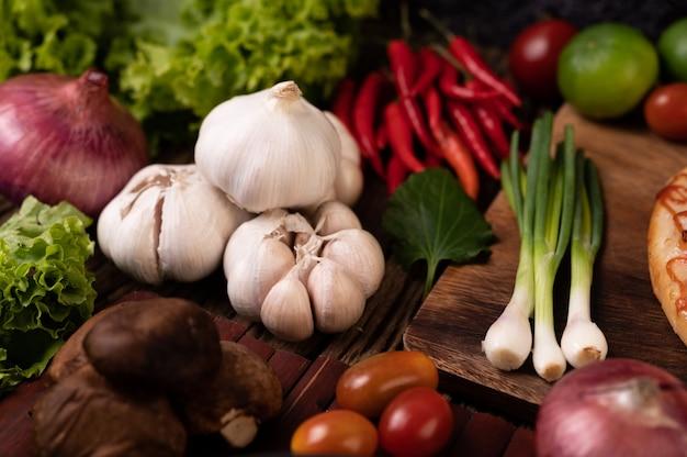 にんにく、トマト、椎茸、唐辛子、赤玉ねぎの木製スラット 無料写真