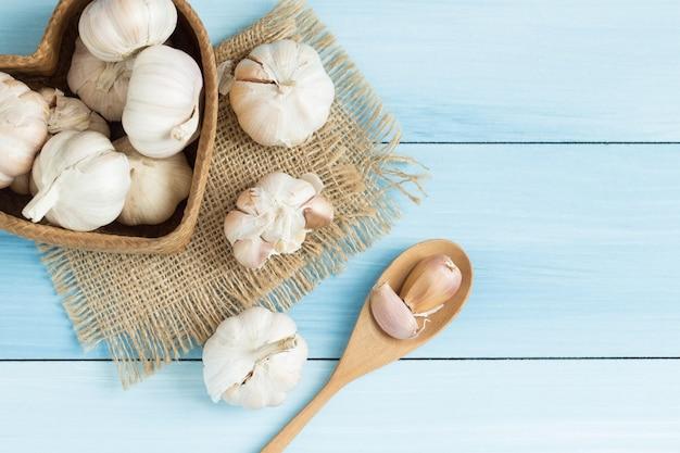 Garlic in a wooden spoon on blue wooden floor,top view Premium Photo