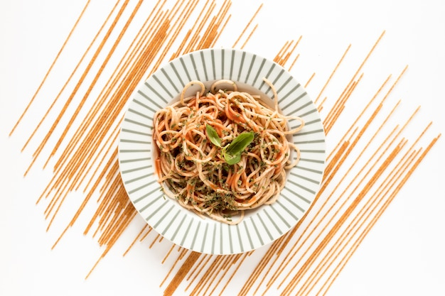 Garnish spaghetti pasta with raw pasta on white surface Free Photo