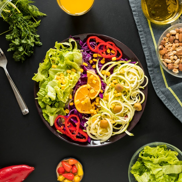 Garnished healthy salad in plate with dryfruits arranged on black background Free Photo