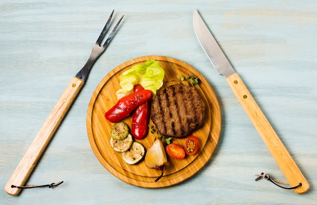 Garnished steak serving with cutlery Free Photo