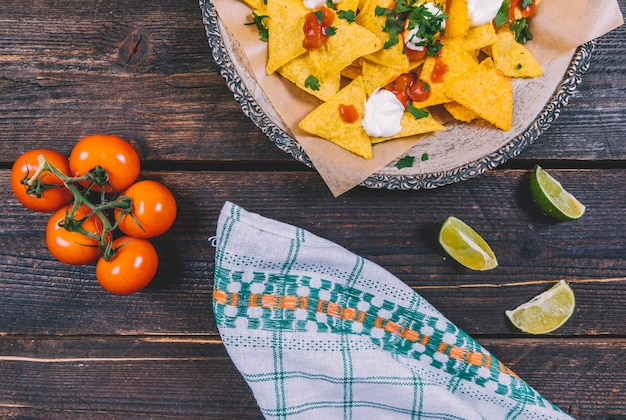 Garnished tasty mexican nachos in plate with lemon slices and cherry tomatoes on brown wooden desk Free Photo