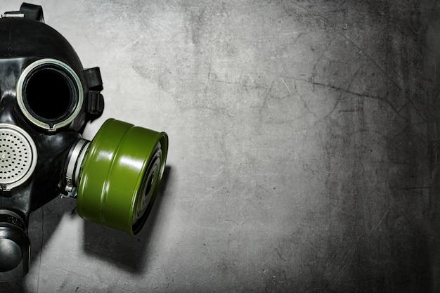 Противогаз на черном фоне камень с зеленым фильтрующий элемент. постапокалиптическая концепция. Premium Фотографии