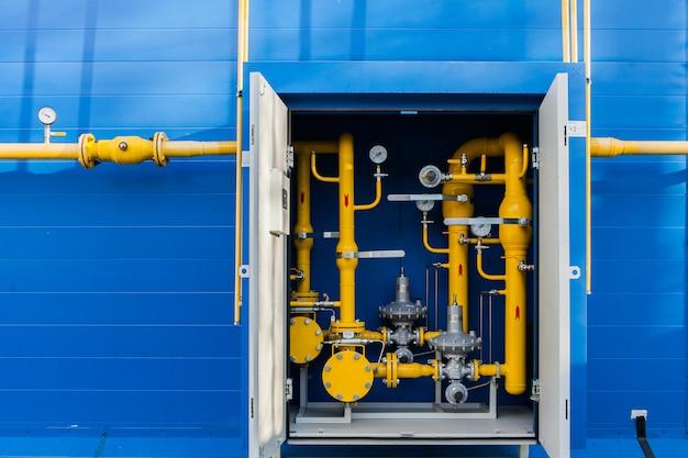 ユーティリティルームの壁にあるガスパイプは、青いサイディングパネルで覆われています。黄色のガスパイプラインバルブがボイラーの奥の部屋にある通信金属製のツールボックスにあります。 Premium写真