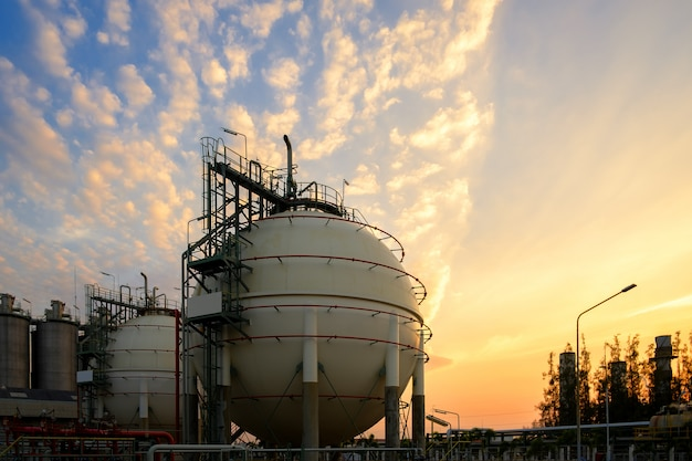 Gas storage sphere tanks and pipeline in petrochemical industrial plant on sky sunset background, manufacturing of petroleum industry plant Premium Photo