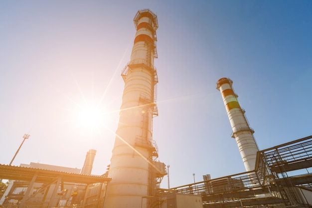 Gas turbine power plant on natural gas with chimneys of red white color against a blue sky on a sunny day Premium Photo