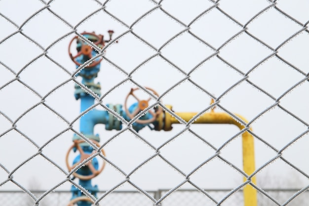 Gas valve with fence in the foreground. Free Photo