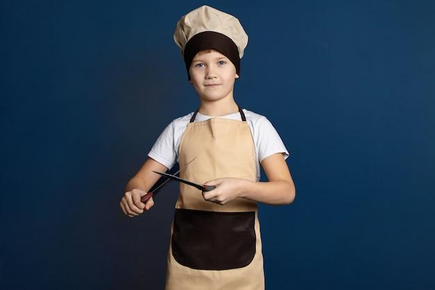 Concetto di gastronomia, cucina, ristorazione e industria alimentare. studio shot di bello carino ragazzo di 10 anni vestito in uniforme da chef affilatura coltello con un altro. coltelli da cucina per affilare i bambini maschi Foto Gratuite