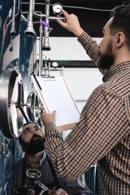 Gauging pressure sensor workers of microbrewery. Premium Photo