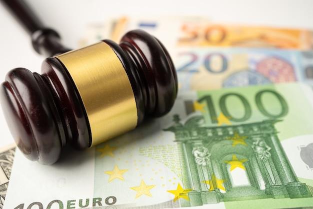 Молоток для судьи-юриста на фоне банкнот евро. Premium Фотографии