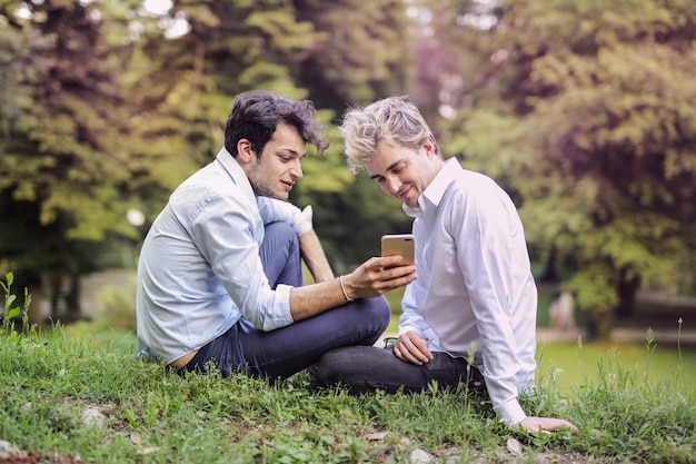 Gay couple checking a smartphone in the park Premium Photo