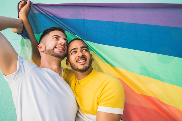 Gay couple embracing and showing their love with rainbow flag. Free Photo