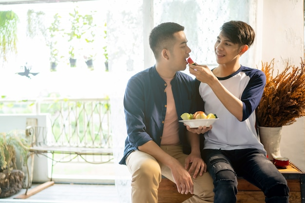 Gay couple is eating fruit with his boyfriend. Premium Photo