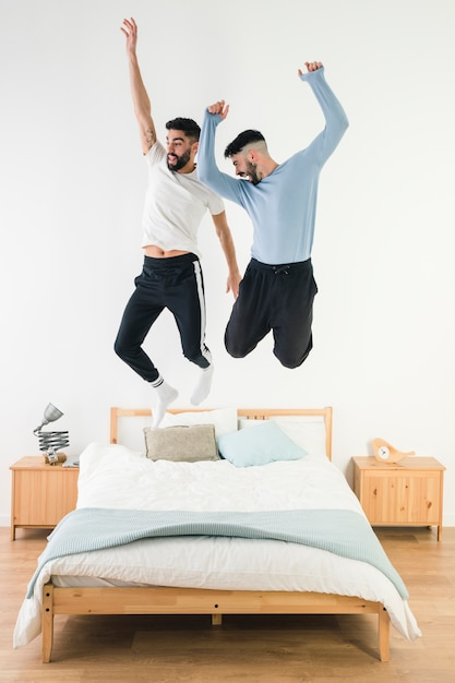 Gay couple jumping on the bed in the bedroom Free Photo