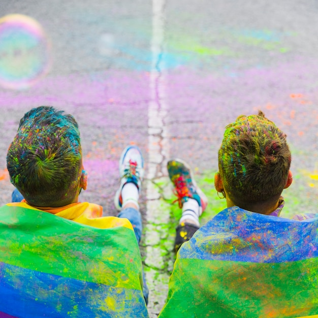 Gay couple sitting on street covered rainbow flag Free Photo