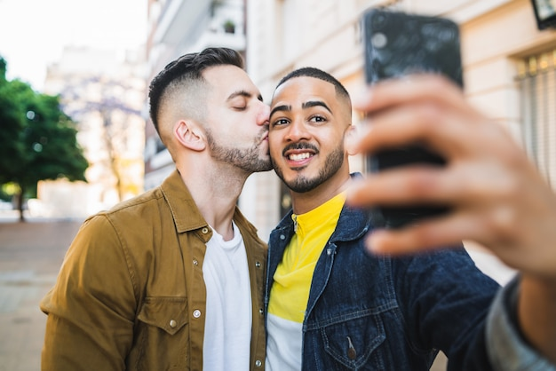 Gay couple taking a selfie in the street. Premium Photo