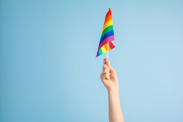 Gay flags in women's hand on grey background Premium Photo
