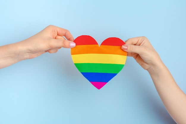 Gay love. human hand holding a rainbow paper heart Premium Photo