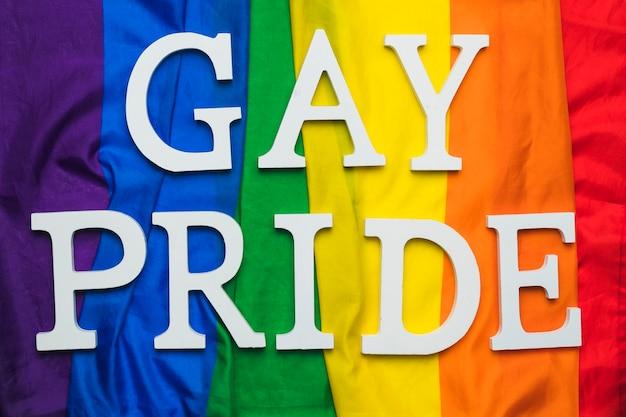 Gay pride lettering on rainbow flag Free Photo