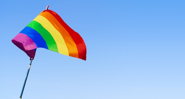 Gay rainbow flag waving in the wind in a clear blue sky Premium Photo