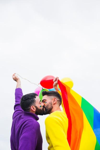 Gay sweethearts kissing on lgbt pride parade Free Photo