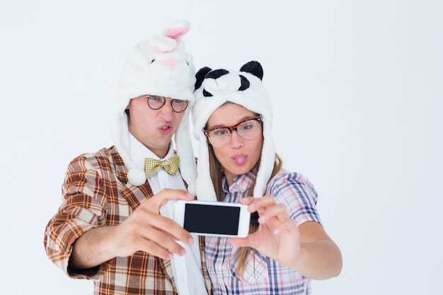 Geeky hipster couple taking selfie with smart phone Premium Photo