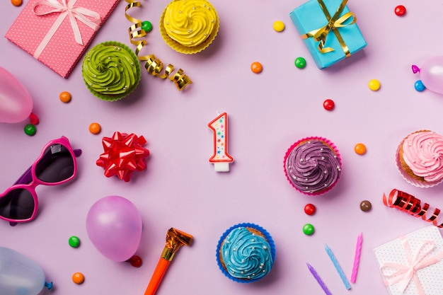 Gems; ribbon bow; ribbon; sunglasses; balloon; muffins on pink backdrop Free Photo