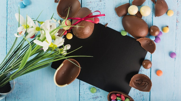 Gentle composition of flowers and chocolate eggs Free Photo