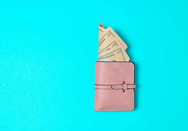 Нежно розовый кошелек с долларами на синем фоне. пойдем по магазинам! Premium Фотографии