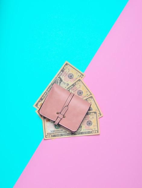 Нежно розовый кошелек с долларами на пастельном фоне. пойдем по магазинам! Premium Фотографии