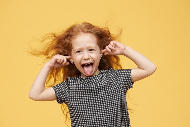 Autentiche emozioni umane, reazione e linguaggio del corpo. bambina viziata arrabbiata con i capelli rossi che sporge la lingua, fingendo di non sentirti, tappando le orecchie, urlando, essendo pazza e cattiva Foto Gratuite