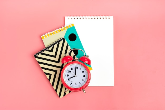 Geometric notebooks and alarm clock on pink stationary, back to school concept  flat lay Premium Photo
