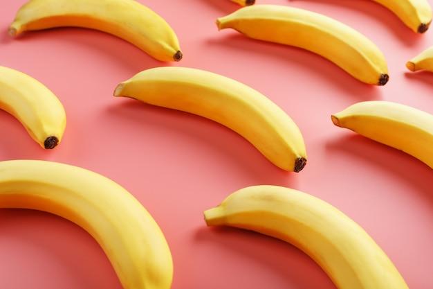 ピンクの背景にバナナの幾何学模様。上からの眺め。最小限のフラットスタイル。ポップアートのデザイン、クリエイティブな夏のコンセプト。 Premium写真