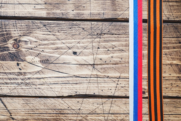 George ribbon and ribbon with russian flag tricolor on wooden background. Premium Photo
