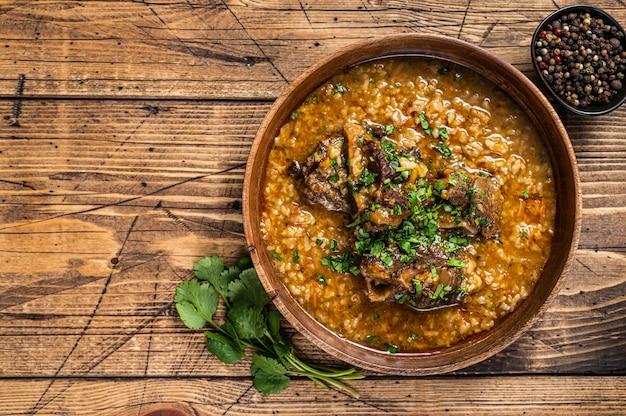 Грузинский суп из баранины харчо с рисом, помидорами и специями в деревянной миске. деревянный Premium Фотографии
