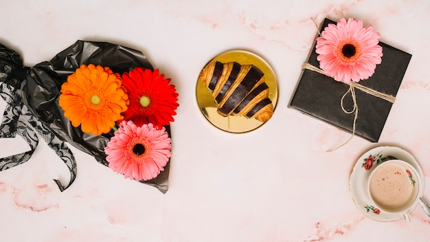 Gerbera flowers on packaging film with gift box and croissant Free Photo