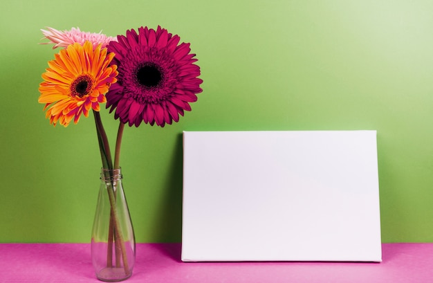 Gerbera flowers in vase near the blank card on pink desk against green wall Free Photo