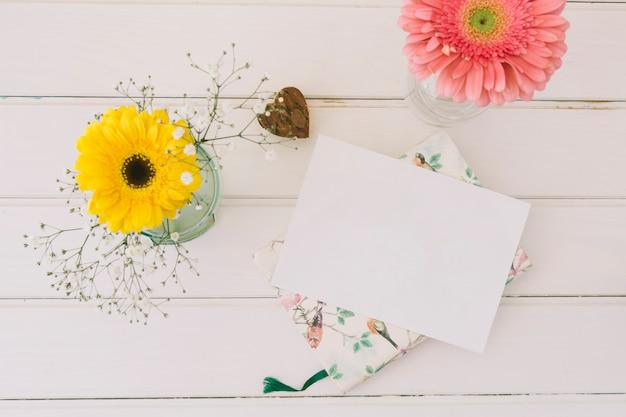 Gerbera flowers in vases with blank paper Free Photo