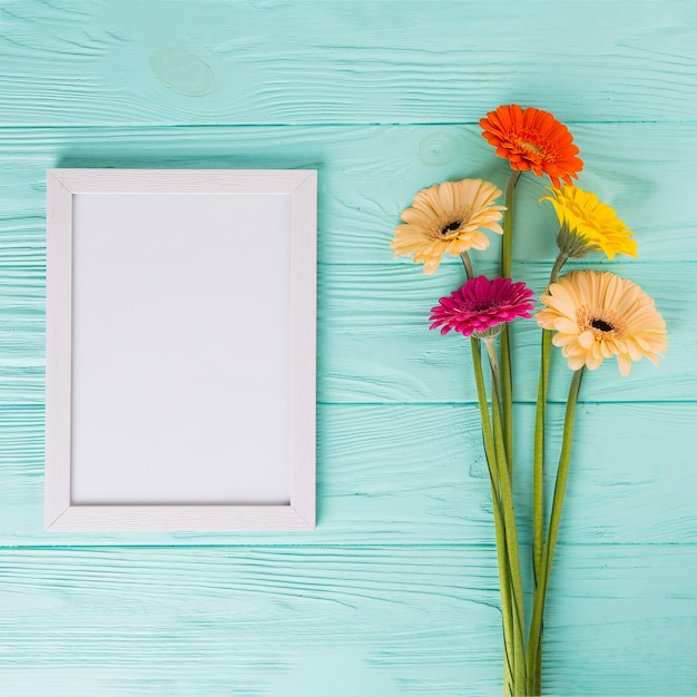 Gerbera flowers with blank frame on table Free Photo