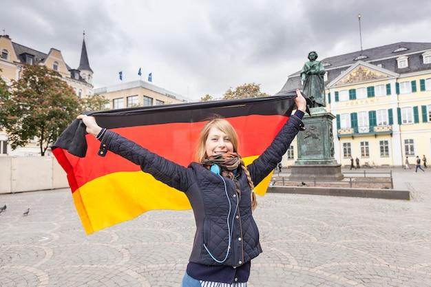 German girl with flag in bonn main square Premium Photo