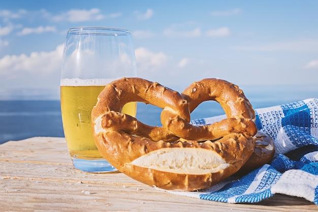German pretzel and glass of beer in sunlight aginst blue sky Premium Photo