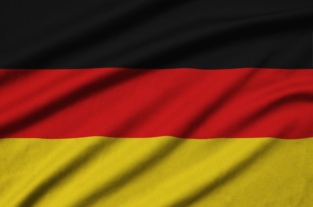 Germany flag is depicted on a sports cloth fabric with many folds. Premium Photo