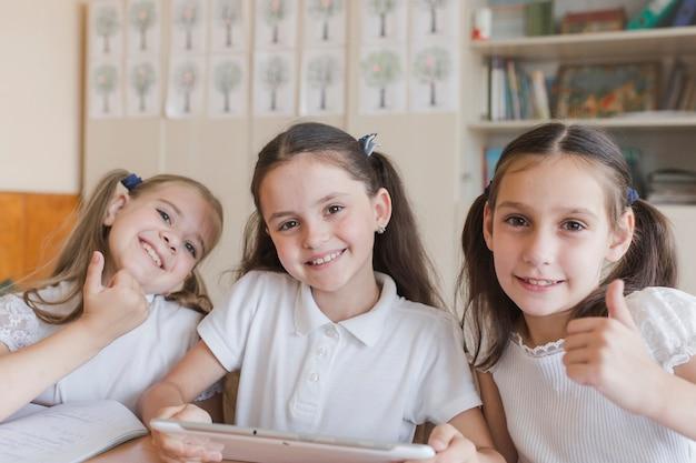 Школьницы с таблеткой gesturing thumb-up Бесплатные Фотографии