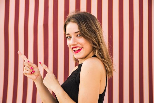 Крупным планом улыбается молодая женщина gesturing Бесплатные Фотографии