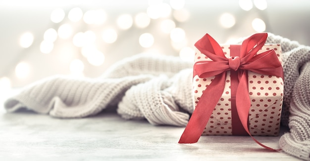Ggift in a beautiful box with a red bow and grey blanket Free Photo