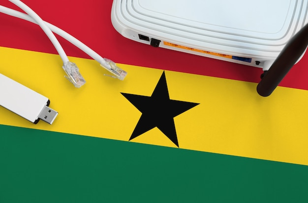 Ghana flag depicted on table with internet  cable, wireless usb wifi adapter and router. internet connection concept Premium Photo
