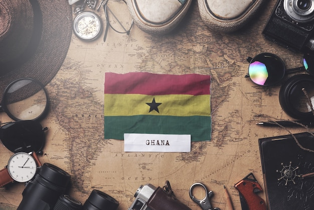 Ghana flag between traveler's accessories on old vintage map. overhead shot Premium Photo