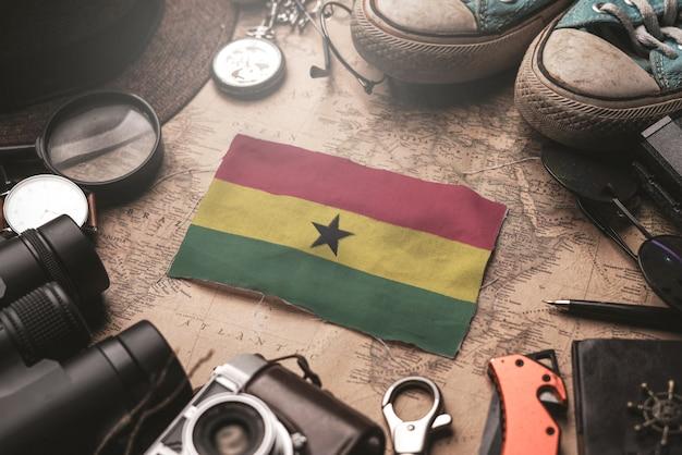 Ghana flag between traveler's accessories on old vintage map. tourist destination concept. Premium Photo