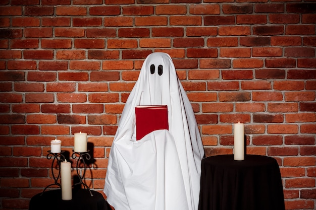 Ghost holding book over brick wall. halloween party. Free Photo