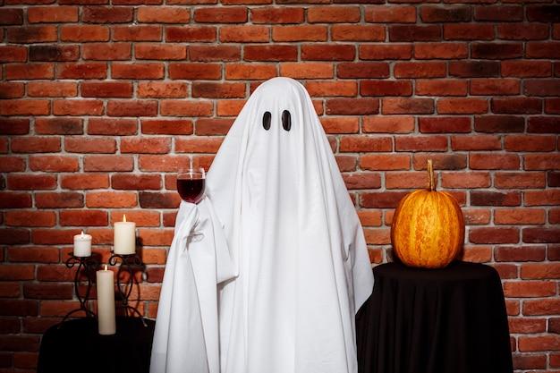 Призрак держит вино над кирпичной стеной Бесплатные Фотографии